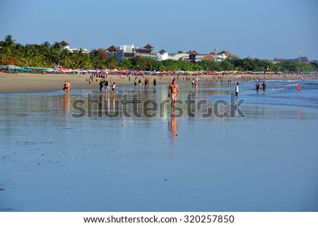 Bali, Indonesia - September 13, 2015: Late Afternoon at Low Tide tourists strolling on Legian Beach. - stock photo
