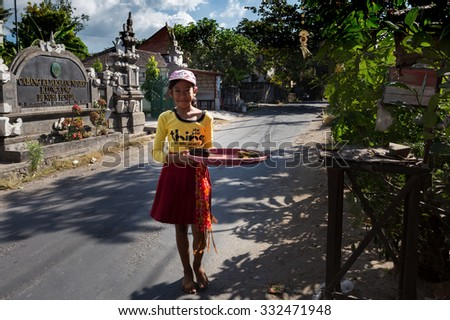 BALI, NUSA PENIDA ISLAND, INDONESIA - JULY 28, 2015: Balinese girl with offerings in front of home temple on July 27, 2015 in Nusa Penida, Indonesia