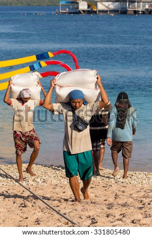 BALI, NUSA PENIDA ISLAND, INDONESIA - JULY 29.2015: Men transports cargo from ship in the hands. There is no other possibility to transport. Nusa Penida July 29. 2015 Indonesia