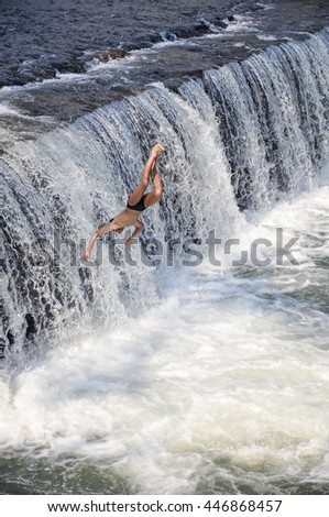 BALI - October  17 : Young man having fun by Jumping water in an artificial dam on the Tukad Unda dam, Bali, Indonesia on October 17 2012