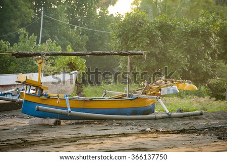 Balinese Fishing Boat. A small, colorful fishing boat, called a jukung, pulled up on the beach in the village of Pemuteran. The fishermen go out in the very early morning hours and return mid morning. - stock photo
