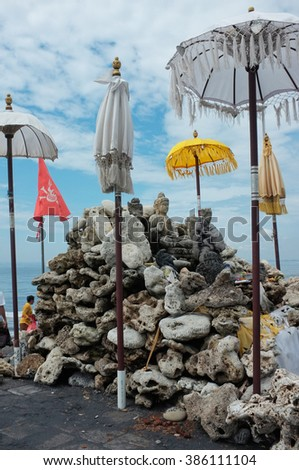 Balinese-Hindu offerings and sculptures of Buddha and Ganesh (Ganesha) form a Hindu-Buddhist shrine to protect the beach from evil and tsunamis at Pantai Purnama in Bali, Indonesia. - stock photo