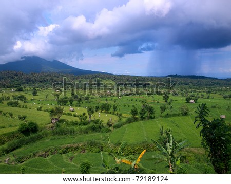 Balinese landscape with rain over rice terraces - stock photo