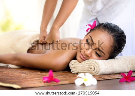 Balinese massage in spa environment,  deep massage of back   - stock photo