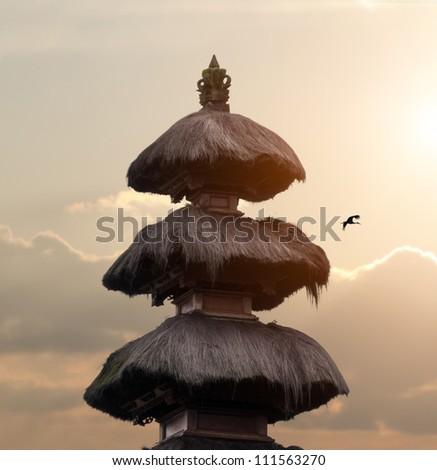 Balinese pagoda top on beautiful sky with sun and stork - stock photo