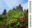 Balinese temple Uluwatu and green lush garden with flowers - stock photo