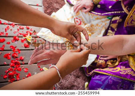 balinese wedding ceremony with human hands - stock photo