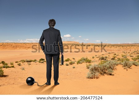 Ball and chain restraining a businessman freedom of decision making.  - stock photo