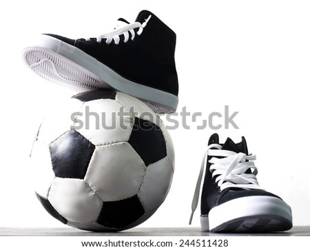 Ball and gym shoes. - stock photo