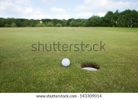 Ball at the hole on empty golf course - stock photo