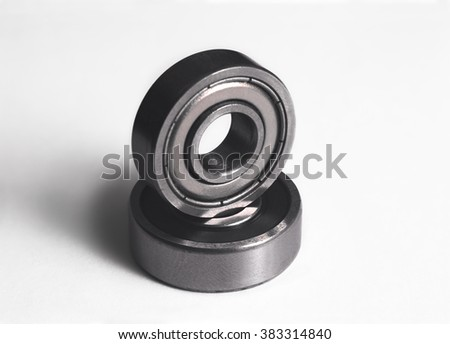 Ball bearing on a white background,  bearing with a long soft shadow,  bearing grey color photo, close-up of ball bearing