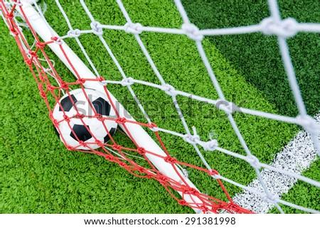 Ball in soccer goal net - stock photo