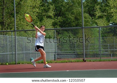 Ball is hit by tennis player.  Female teen runs to return volley during game. - stock photo