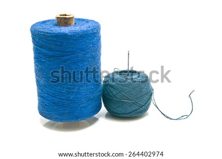 ball of black yarn and spool of thread on white - stock photo