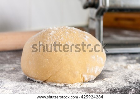 Ball of fresh fresh pasta dough on a floured surface - stock photo