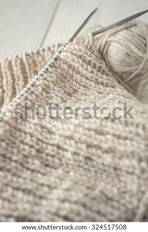 Ball of gray yarn and knitting on white table