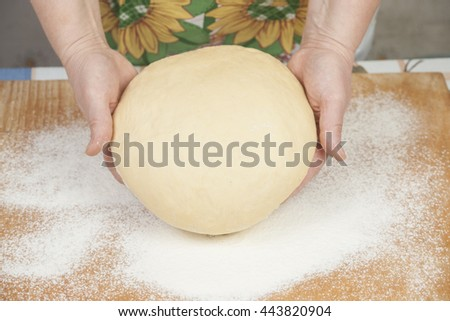 Ball of pizza dough with flour on the wooden table - stock photo