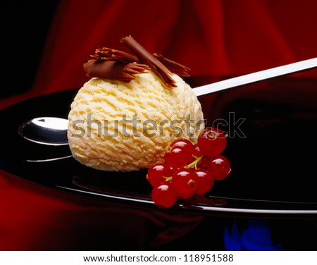 Ball of vanilla ice cream with chocolate curls and currants on a plate - stock photo