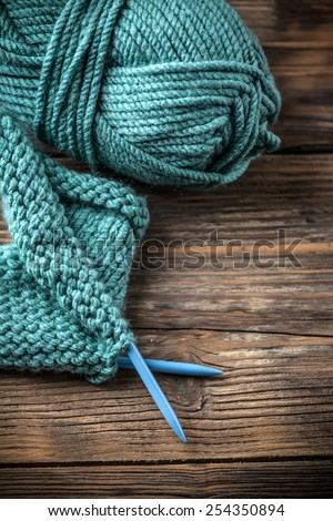 Ball of yarn and knitting on wooden board - stock photo