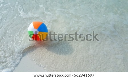 Ball on a white sandy beach white clear water background