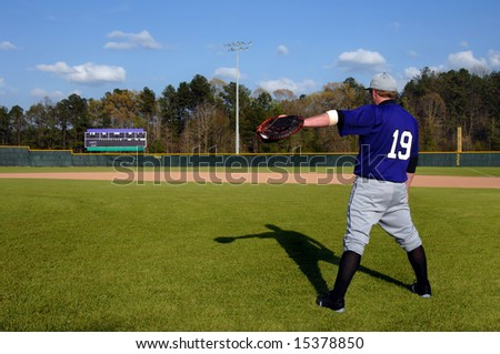 Ball player throws a tall shadow and gives his all to his favorite game.  He faces scoreboard.