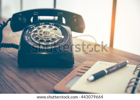 Ball point pen on notebook with old black phone background, retro style concept  - stock photo
