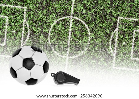Ball, referee whistle, and a fragment of a football pitch with markings - stock photo