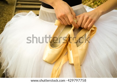 ballerina holding ballet shoes.Ballet shoes in the hand of the girl, outdoors.ballerina in a tutu