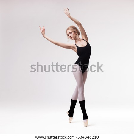 Ballerina in black outfit posing on toes over light grey studio background