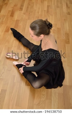 Ballerina in black sitting on the floor and trying on a pointe