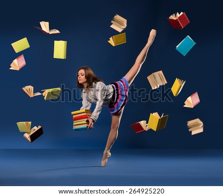 Ballerina in form of  schoolgirl with pile heavy books, and flying books around - stock photo