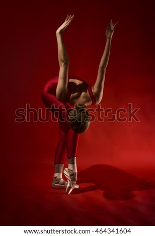 Ballerina in red outfit posing on toes, studio shot on red background. Young beautiful dancer posing in studio
