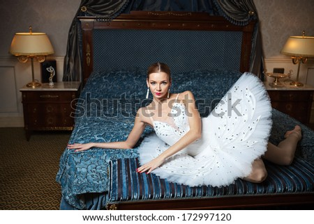 Ballerina lying down on bed and daydreaming in luxury interior  - stock photo