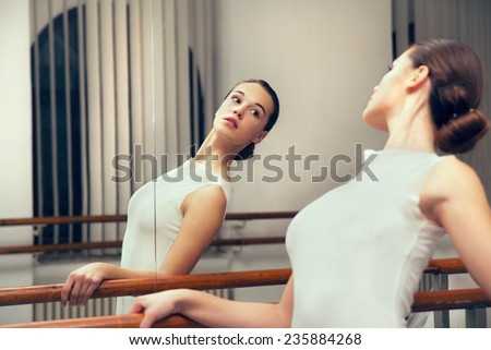 Ballerina posing, reflection in the mirror on the background - stock photo