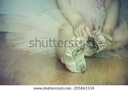 ballerina puts on pointe - stock photo