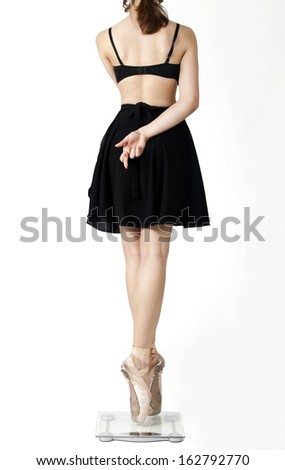 Ballerina's feet on scale on a white background. - stock photo