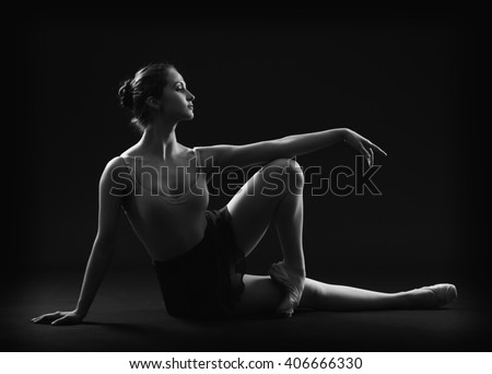 Ballerina sitting in an elegant pose. Black and white photo. - stock photo
