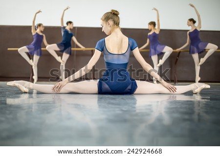 ballerina sitting on the floor with his back to the camera in the splits and dance class dancers practicing on the background - stock photo