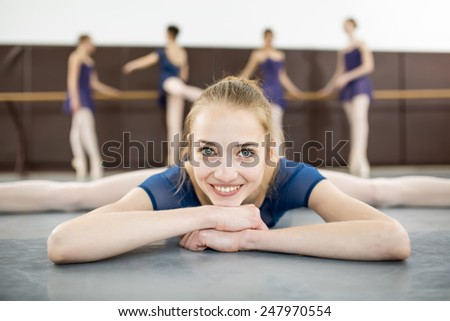 ballerina sitting on the floor with his face to the camera in the splits and dance class dancers practicing on the background - stock photo