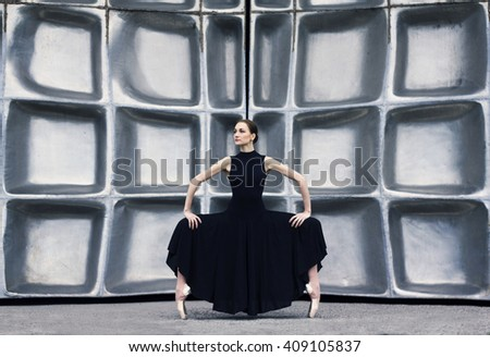 Ballerina  stands in dance pose  on the building background.