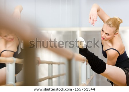 Ballerina stretches herself near barre and mirrors in the classroom - stock photo