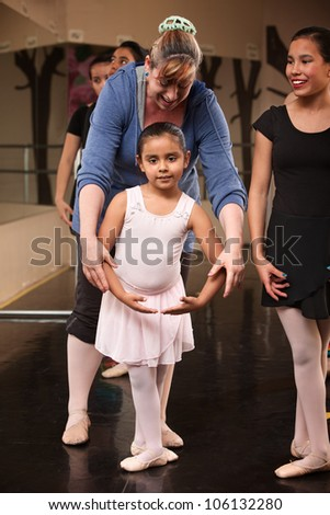 Ballet class instructor helps young student with fourth position - stock photo