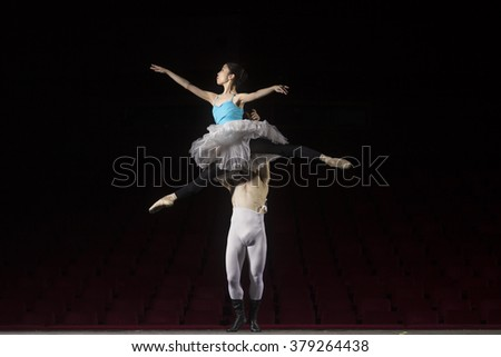 Ballet dance couple, practising. On stage in theater.