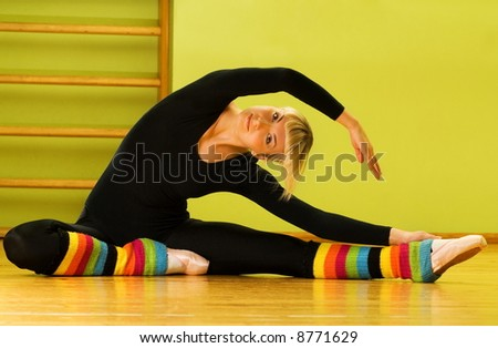 ballet dancer doing stretching exercise on stock photo