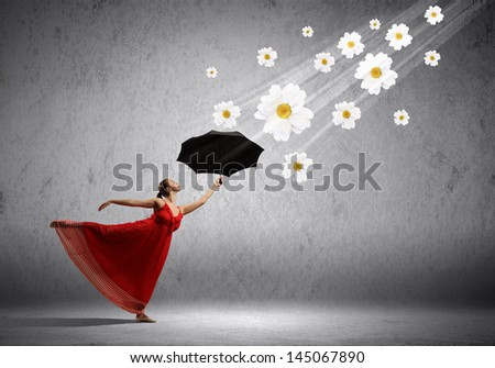 ballet dancer in flying satin dress with umbrella and flowers - stock photo