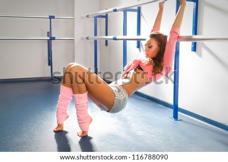 Ballet dancer relaxing after exercise by bar in dance studio - stock photo