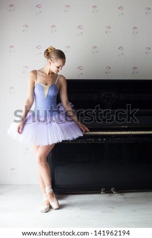 Ballet dancer touching piano, studio shot - stock photo