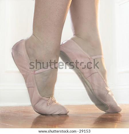 Ballet feet in Releve on a hardwood dance floor - stock photo