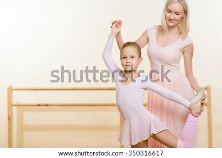 Ballet lesson. Young female teacher helping her little apprentice to learn new move and hold the pose.
