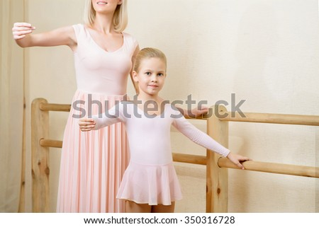 Ballet pose. Young female ballet teacher and her little apprentice are standing in the same ballet pose.